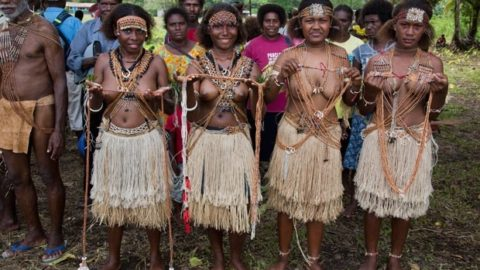 Kate's smiles as she's greeted by topless tribal women